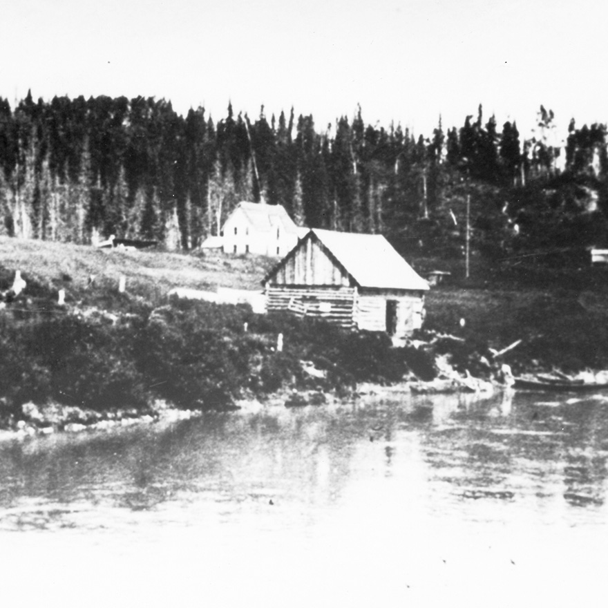 Black and white photo showing a small wooden cabin on a riverbank and a white two-story house on the hillside behind it. A forest of tall trees in the background.